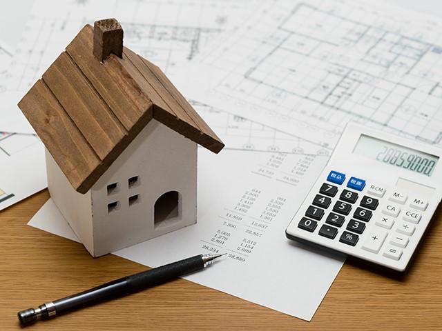 住宅模型、間取図、電卓と鉛筆