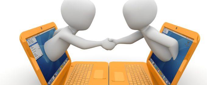 握手するパソコンから飛び出た2人